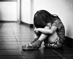 The Alchemy of Adversity - A woman sitting on the floor - Childhood trauma