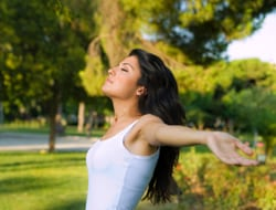 Success Stories - A woman standing in the grass - Plastic surgery